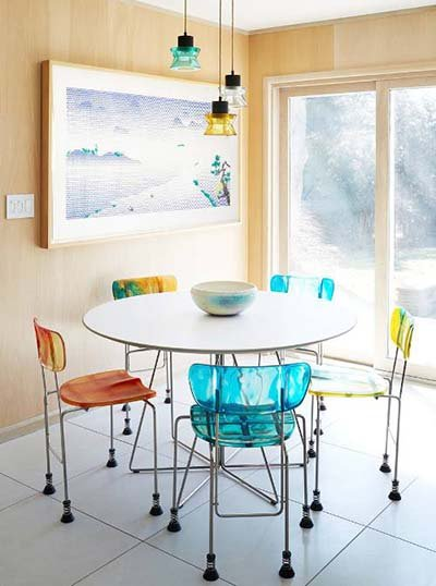 Five multicolored Broadway Chairs surround a white round dining table