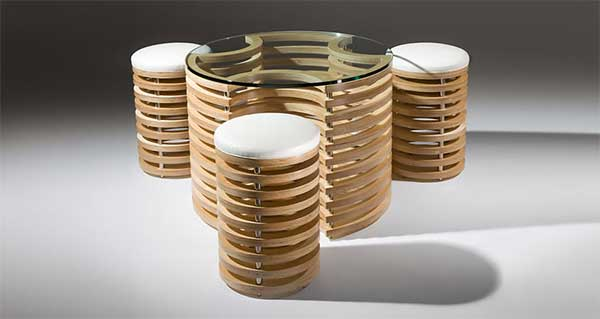 A cylindrical coffee table with a glass top that can house the three cylindrical wood stools with white seat cushion