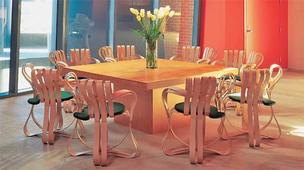 Gehry Cross Check Chair Set featuring 8 chairs made with ribbons of wood set around a wooden square table