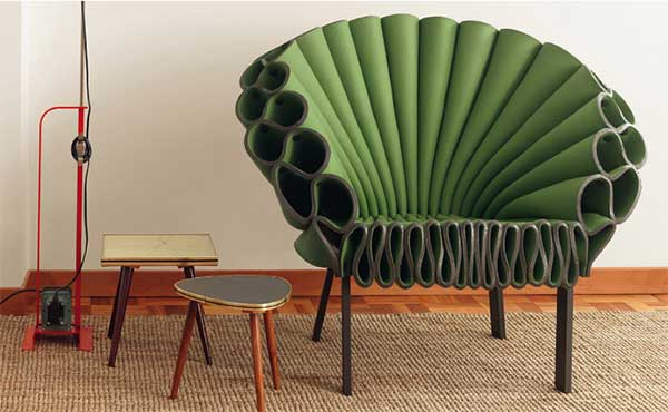 A green Peacock Chair with small side tables on the left