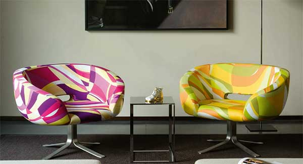 Two Rive Droite Lounge Chairs, with the left chair featuring a blend of pink, purple, white, and yellow colors, and the right chair featuring a mix of yellow, green, orange, and white
