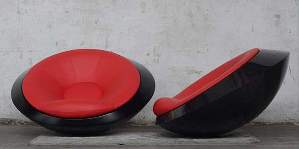 A UFO-like chair with spherical black bottom and red beanbag-like cushion