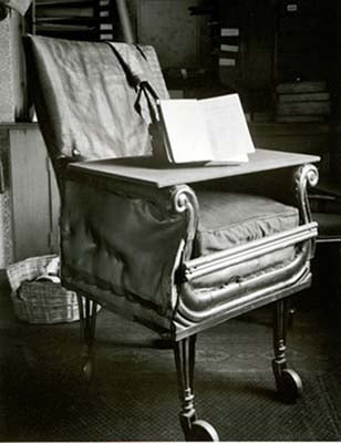 A black and white image of Charles Darwin's office chair, made of wood and upholstered seat cushion and wheels