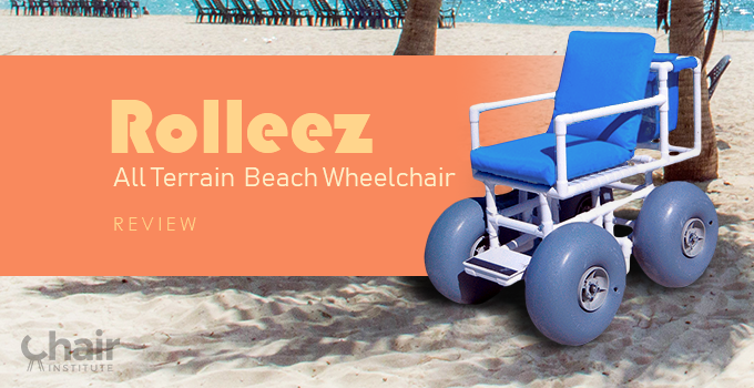 The Rolleez All Terrain Beach Wheelchair on a sandy beach under a coconut tree with beach chairs in the background