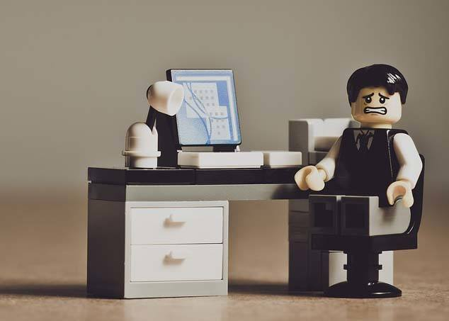 A Lego Businessman Sitting In Despair In His Desk